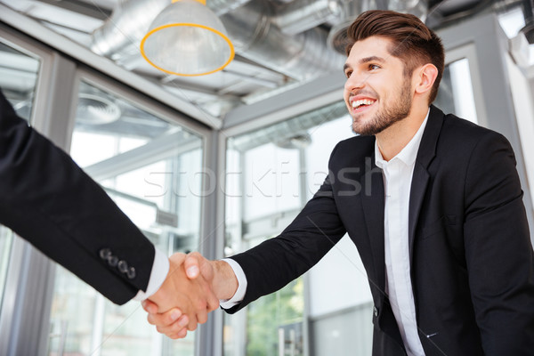 Two successful businessmen shaking hands on business meeting in office Stock photo © deandrobot