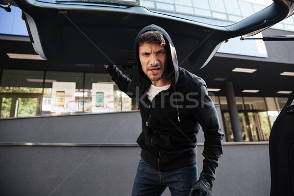 Irritated criminal man standing and closing car trunk outdoors Stock photo © deandrobot