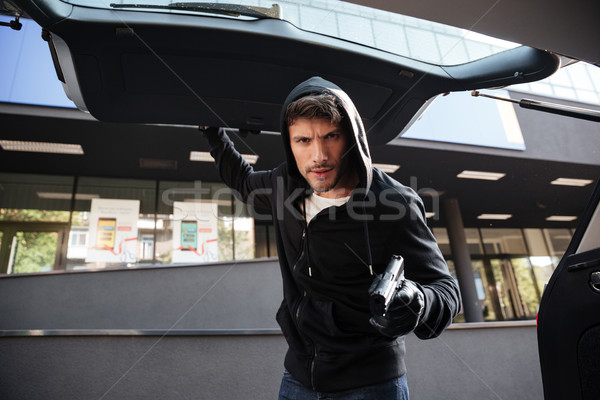 Criminal man threatening with gun and closing car trunk outdoors Stock photo © deandrobot