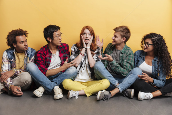 Surpsised redhead young woman sitting with her friends Stock photo © deandrobot