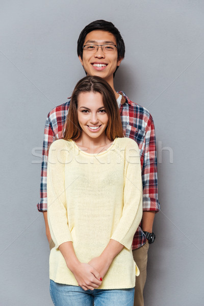 Smiling cheerful interracial couple standing together and looking at camera Stock photo © deandrobot