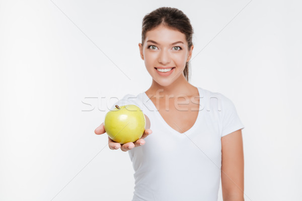 Cheerful woman holding apple and showing to camera. Stock photo © deandrobot
