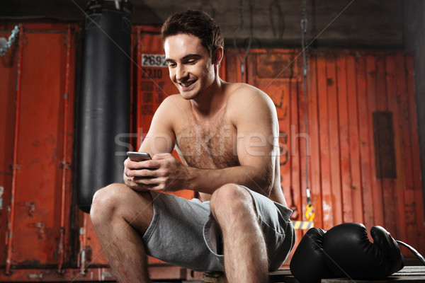 Cheerful man sitting in a gym while chatting by phone. Stock photo © deandrobot