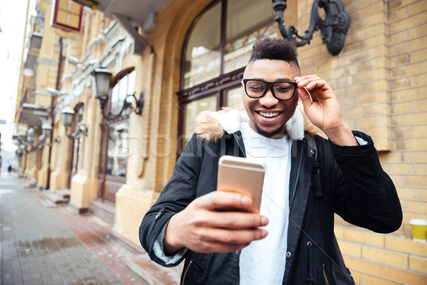 African cheerful man holding cellphone and make selfie outdoors. Stock photo © deandrobot