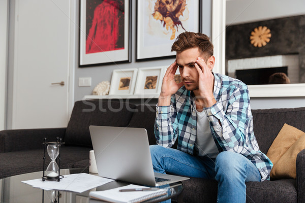 Stressful bristle man with headache using laptop computer Stock photo © deandrobot