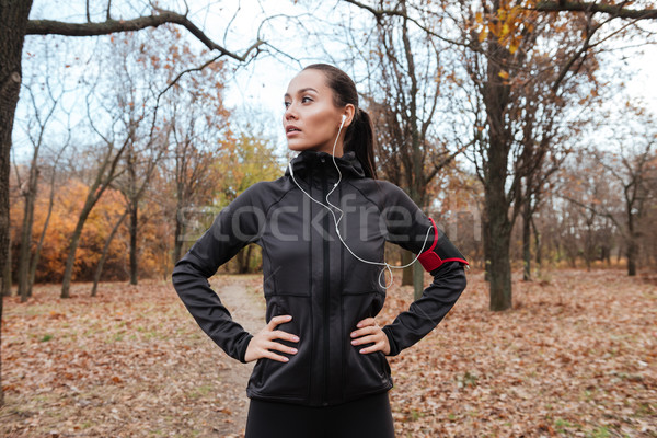 Young runner in warm clothes and headphones looking aside Stock photo © deandrobot