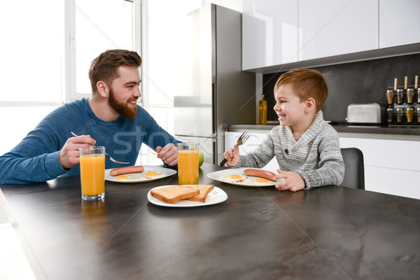 Happy bearded father eating at kitchen with his little son Stock photo © deandrobot