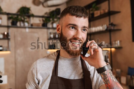 Happy young man buying wine and talking on cell phone Stock photo © deandrobot