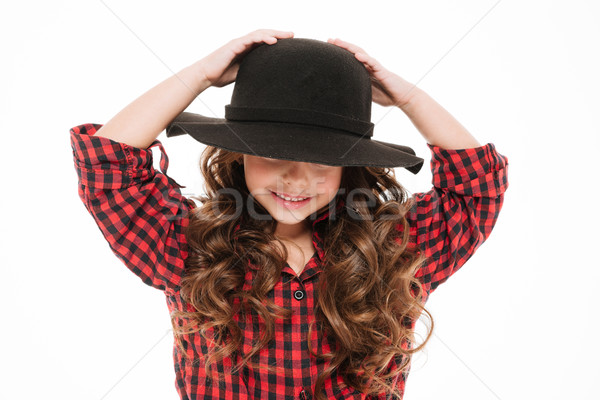 Cute amusing little girl in hat standing and having fun Stock photo © deandrobot