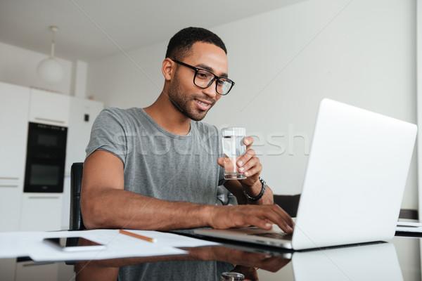 Stockfoto: Vrolijk · afrikaanse · man · drinkwater · met · behulp · van · laptop · grijs