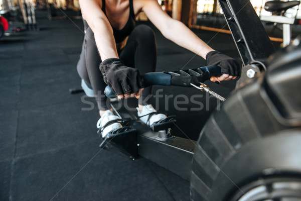Stock photo: Woman athlete working out using fitness equipment in gym