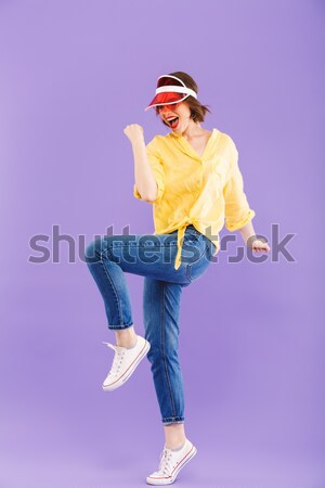 Cheerful playful young fitness woman holding skateboard and having fun Stock photo © deandrobot