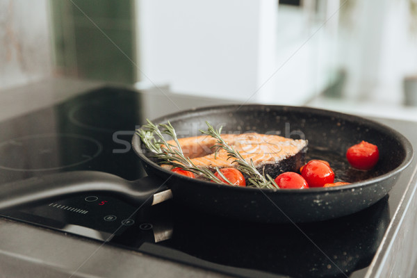 Fish and vegetables on frying pan in kitchen. Cooking concept. Stock photo © deandrobot