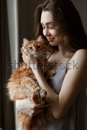 Vertical image of pretty woman in nightie kissing cat Stock photo © deandrobot
