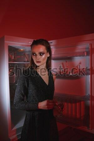 Vertical image of woman standing near the fridge Stock photo © deandrobot