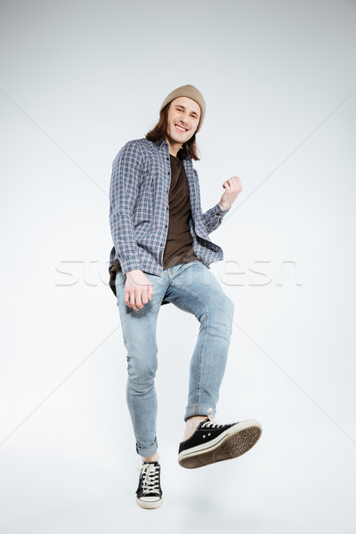Vertical image of hipster playing on imaginary guitar Stock photo © deandrobot