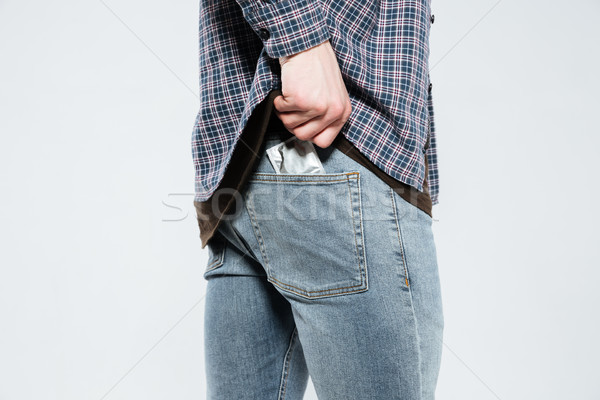 Cropped image of hipster laying condom in back pocket Stock photo © deandrobot