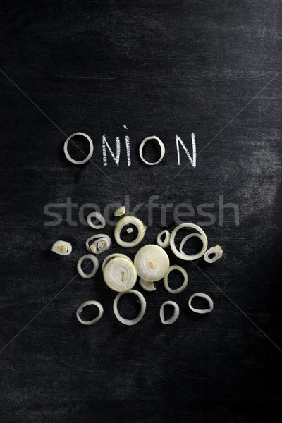 Cut onion over dark chalkboard background Stock photo © deandrobot