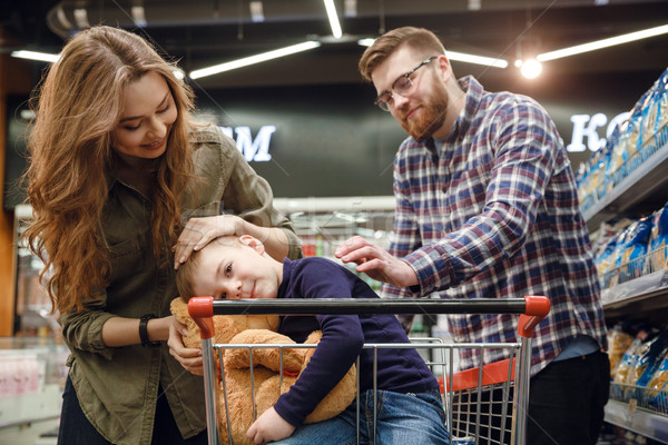 Young boy sitting in shopping trolley in supermarket Stock photo © deandrobot