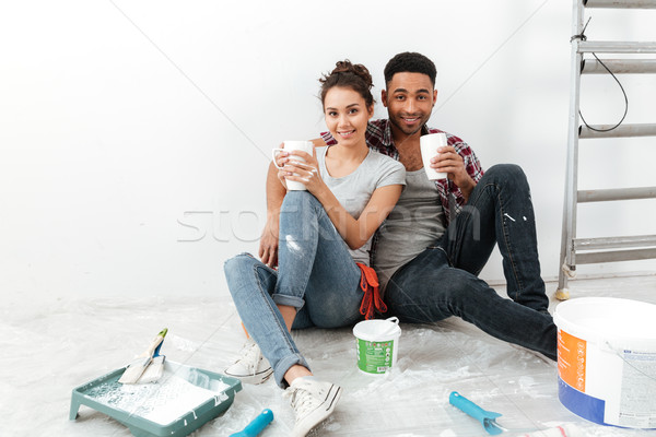 Happy beautiful young couple drinking coffee and renovating home Stock photo © deandrobot