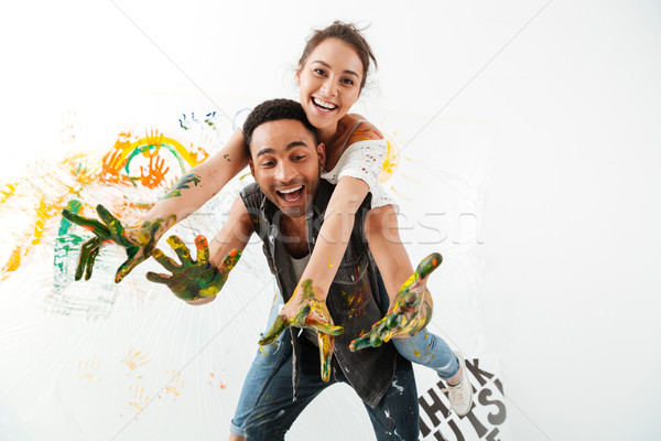 Cheerful couple with hands dirty in paints laughing and painting Stock photo © deandrobot