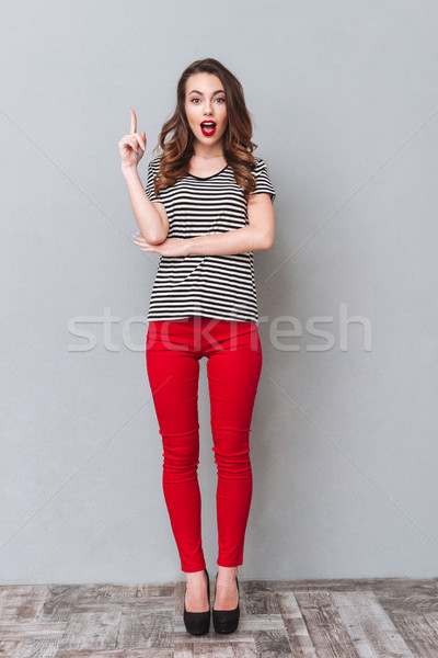 HAppy young lady standing over grey wall have an idea Stock photo © deandrobot