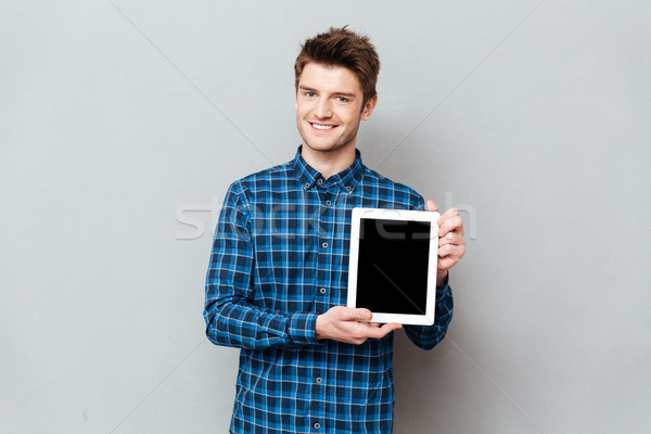 Young man showing blank screen of tablet computer isolated Stock photo © deandrobot