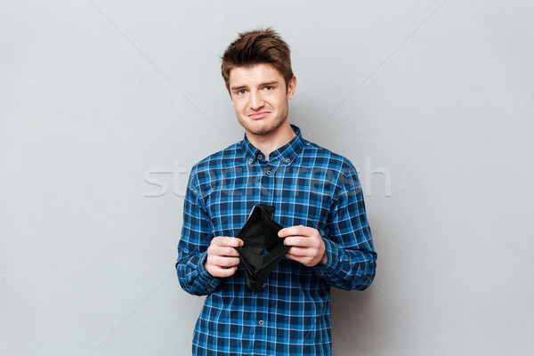 Sad man standing over grey wall holding purse without money. Stock photo © deandrobot