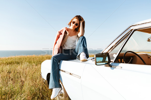 Stock photo: Stylish pretty woman relaxing while sitting on a car outdoors