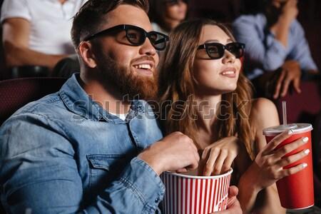 Loving couple friends sitting in cinema watch film Stock photo © deandrobot