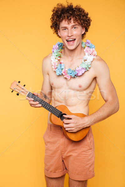 Young shirtless guy holding ukulele and looking at camera Stock photo © deandrobot