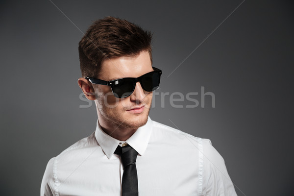 Portrait of a stylish young man in sunglasses looking away Stock photo © deandrobot