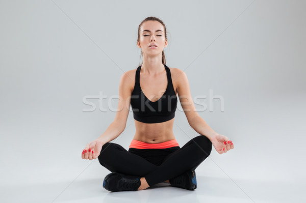 Young concentrated fitness woman sitting on the floor Stock photo © deandrobot
