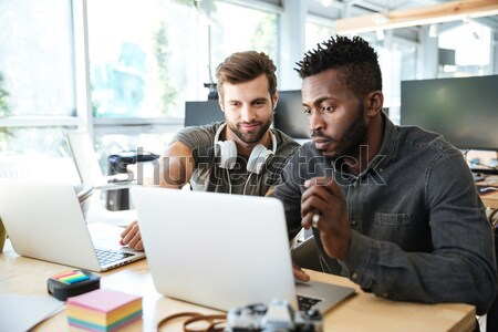 Happy young colleagues sitting in office coworking using laptop Stock photo © deandrobot