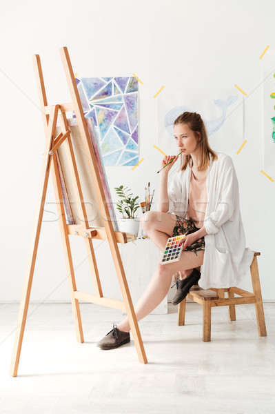 Concentrated young caucasian lady painter at workspace Stock photo © deandrobot