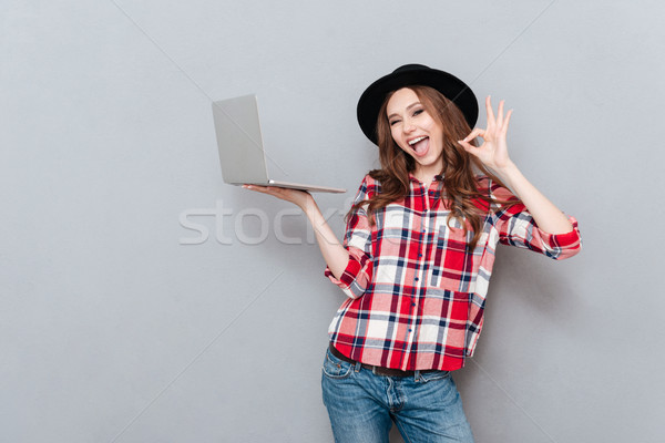Portrait of an attractive woman in plaid shirt holding pc Stock photo © deandrobot