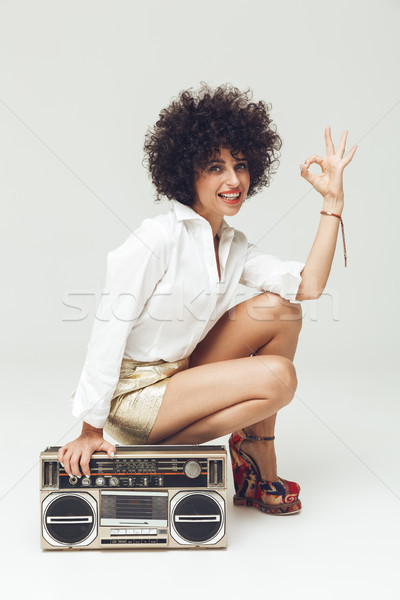 Pretty retro woman near boombox showing okay gesture. Stock photo © deandrobot