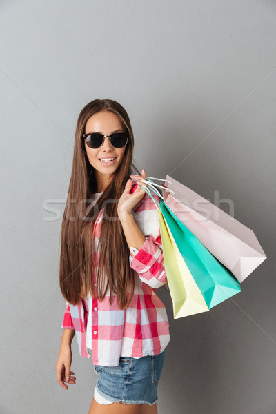 Portrait of young smiling woman in glasses holding colourful sho Stock photo © deandrobot
