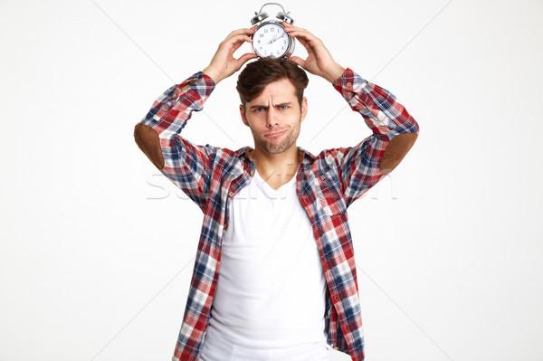 Portré fiatal vicces férfi tart ébresztőóra Stock fotó © deandrobot