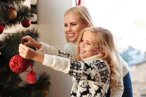 Stock photo: Happy mother and little daughter decorating christmas tree at ho