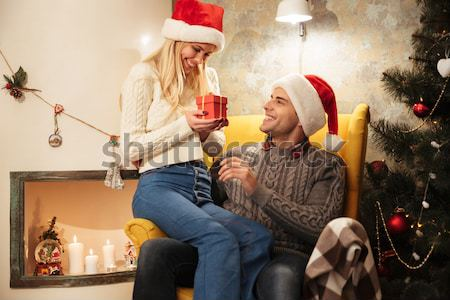 Overjoyed pretty blonde woman holding present looking at ger hus Stock photo © deandrobot