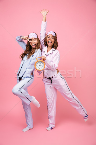 Pretty funny friends women in pajamas holding alarm clock Stock photo © deandrobot