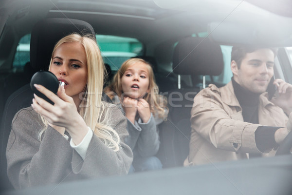 Woman doing makeup look at mirror sitting in car Stock photo © deandrobot