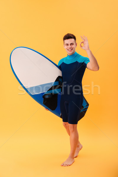 Full length image of happy surfer walking with surfboard Stock photo © deandrobot