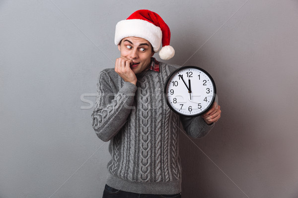 Intrigued man in sweater and christmas hat holding clock Stock photo © deandrobot