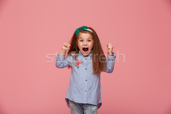 Beautiful female kid in hair hoop and fashion clothes clenching  Stock photo © deandrobot