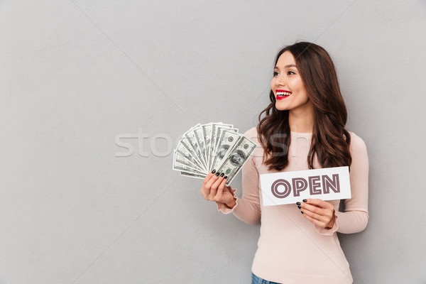 Half-turn image of lucky woman holding open sign and fan of mone Stock photo © deandrobot