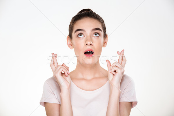 Portrait of praying young female wearing casual shirt wishing so Stock photo © deandrobot