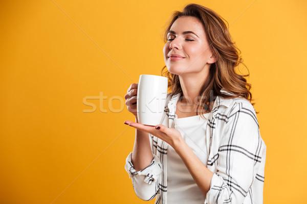 Gyönyörű fiatal nő tart csésze tea csukott szemmel Stock fotó © deandrobot
