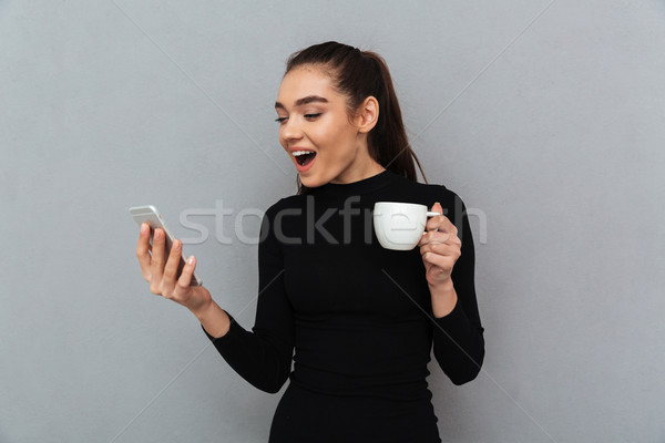 Surprised happy brunette woman in black clothes looking at smart Stock photo © deandrobot